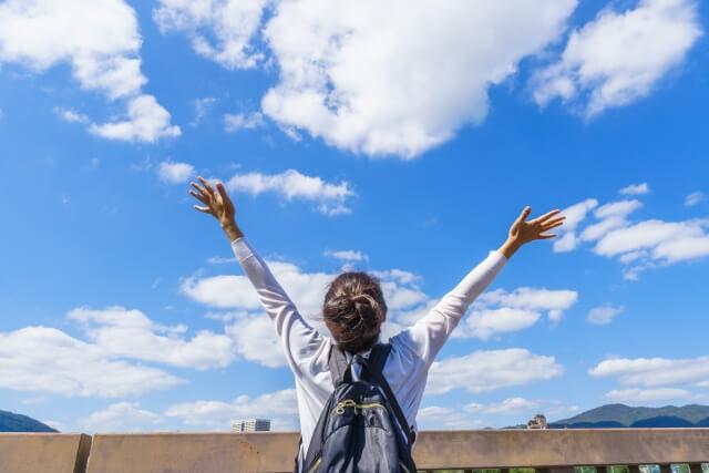 空に手を広げる女性